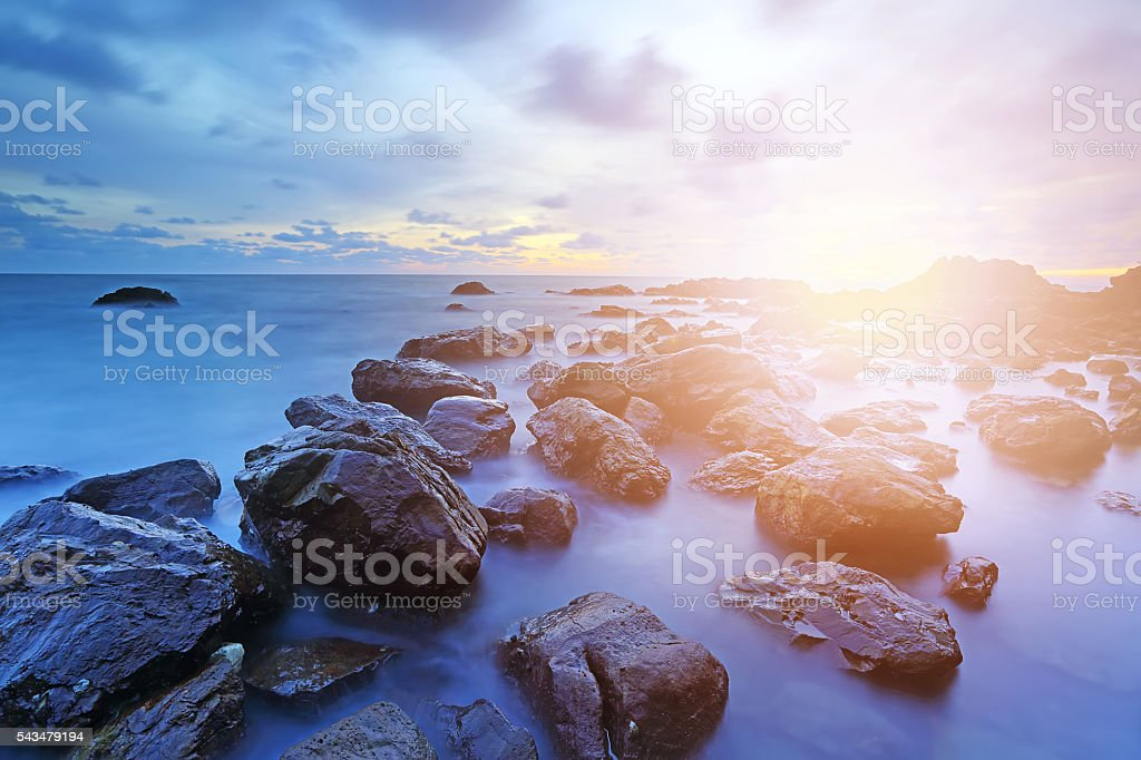 Colorful landscape, Soft setting sun on sea and rocks stock photo