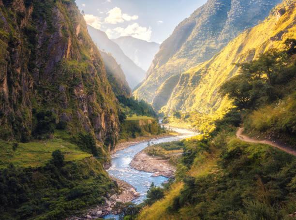 bunte landschaft mit hohen himalaya-gebirge, schön geschwungene fluss, grünen wald, blauer himmel mit wolken und gelben sonnenlicht bei sonnenuntergang im sommer in nepal. bergtal. reisen im himalaya - bach stock-fotos und bilder