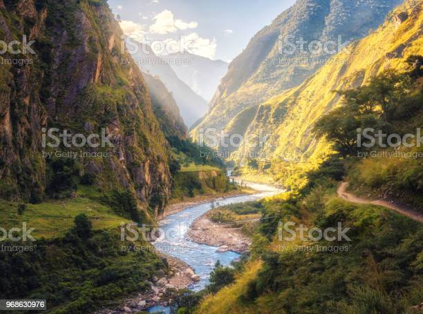 Photo of Colorful landscape with high Himalayan mountains, beautiful curving river, green forest, blue sky with clouds and yellow sunlight at sunset in summer in Nepal. Mountain valley. Travel in Himalayas
