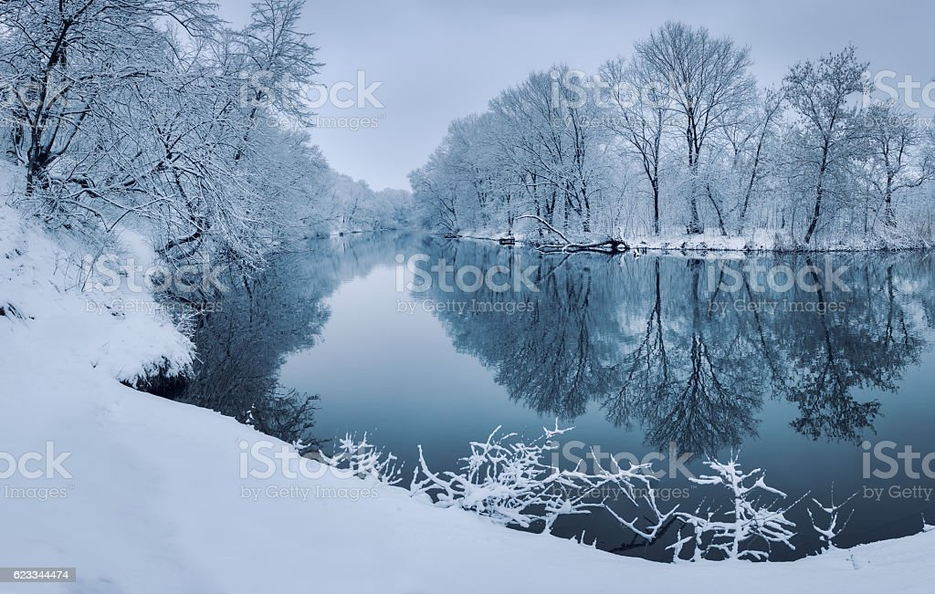 Colorful landscape with snowy trees, beautiful frozen river at sunset stock photo