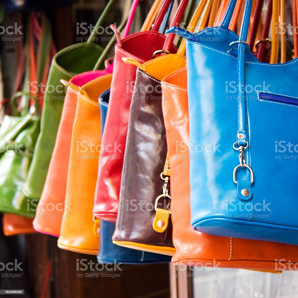 Colorful large hand bags hanging from rack royalty-free stock photo
