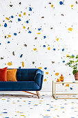 istock Colorful lastrico stickers pattern on a white wall and floor of a modern living room with a navy peony sofa. Real photo. 1034939192