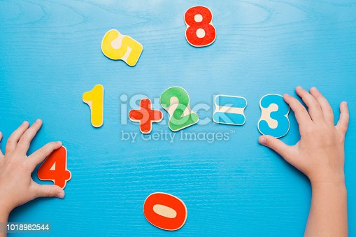 istock Colorful learning numbers for little kids on the blue table. Girl's hand putting number three. Right answer. Time to learn. Education concept. Top view. 1018982544