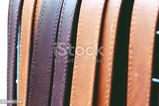 istock Colorful leather belts on rack close up 1136931229
