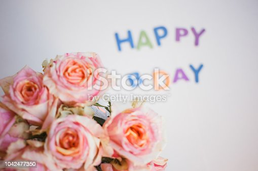 istock colorful letters happy birthday and roses bouquet. congratulation background 1042477350