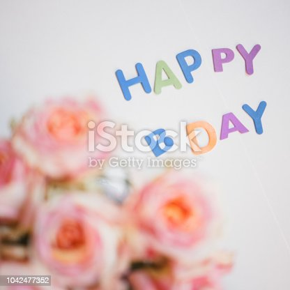 istock colorful letters happy birthday and roses bouquet congratulation background 1042477352