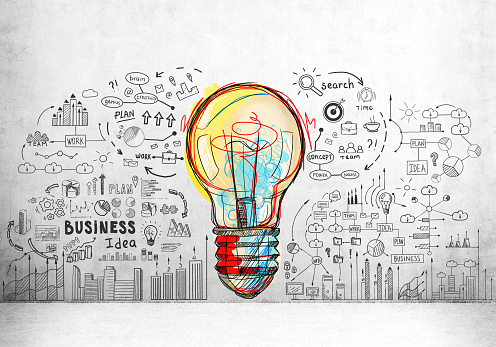Large and colorful light bulb sketch surrounded by smaller business icons and words drawn on a concrete wall.
