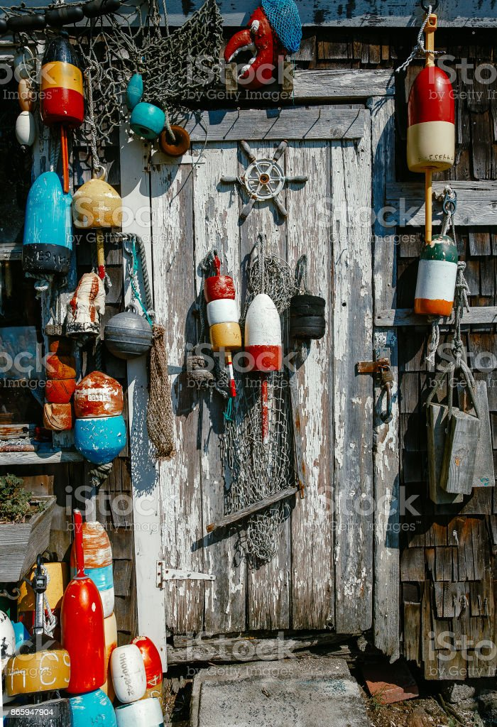 colorful lobster buoys on the wooden wall of the house stock photo