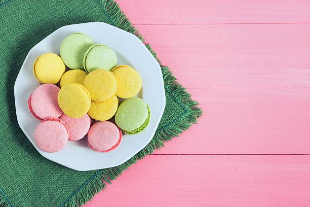 colorful macaron in a plate on wooden, pink background. selective - spitzenkekse stock-fotos und bilder