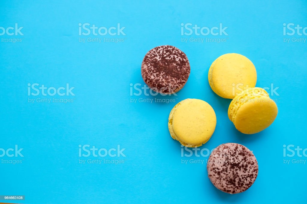 Colorful macarons cake, top view flat lay, sweet macaroon on color blue candy isolated background. Minimal concepts pattern above, food background. Copy space . French dessert. royalty-free stock photo