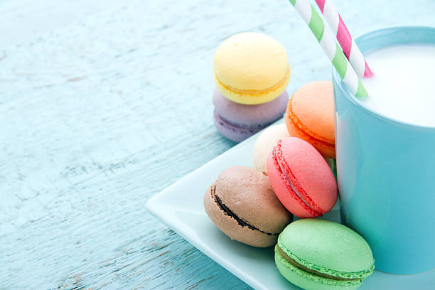 Colorful macaroons and a cup of milk stock photo