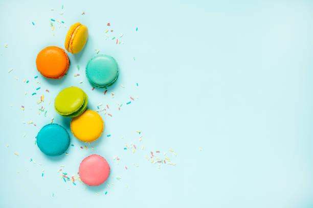 confeitos coloridos e polvilha açúcar dispostas sobre fundo azul. copie o espaço. - macaroon - fotografias e filmes do acervo