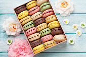 Colorful macaroons in a gift box and roses