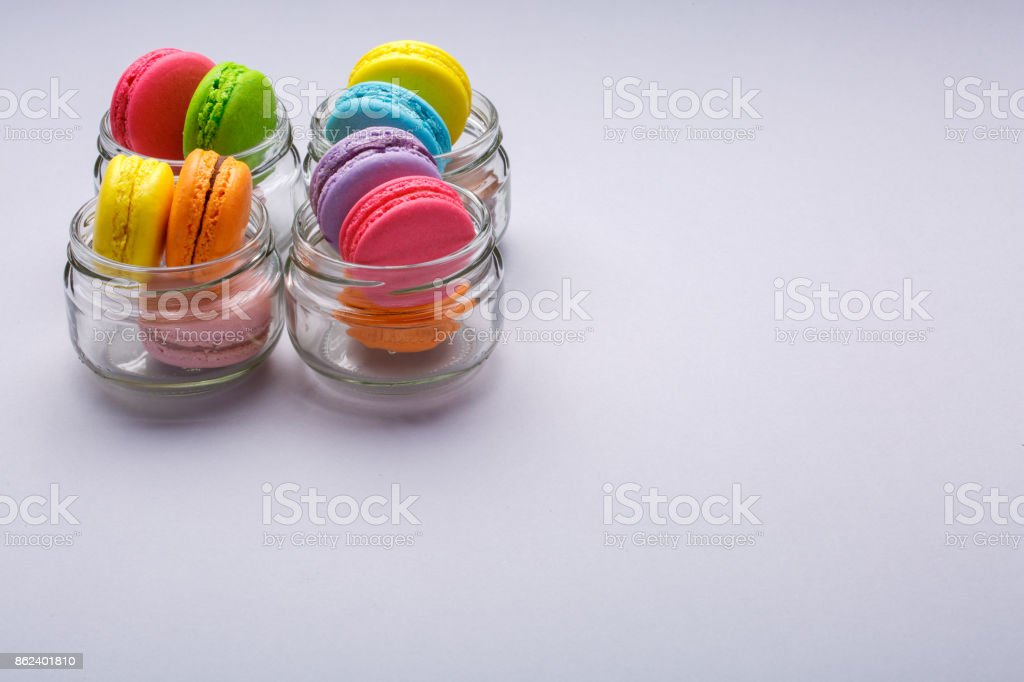 Colorful Macaroons in four clear glasses. Place for the text stock photo