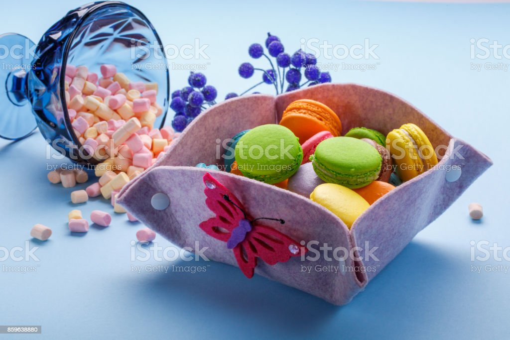 Colorful macaroons over blue background and marshmallow pouring out of the blue vase. Sweet macaroons in gift box. stock photo