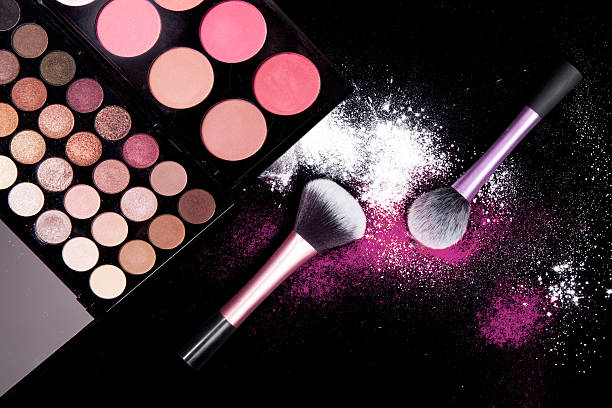 Colorful makeup palette and brush to apply powder on black. – zdjęcie