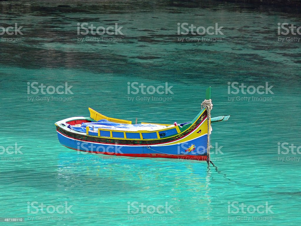 Colorful Maltese fisherman's boat 'Iuzzu' in crystal clear water stock photo