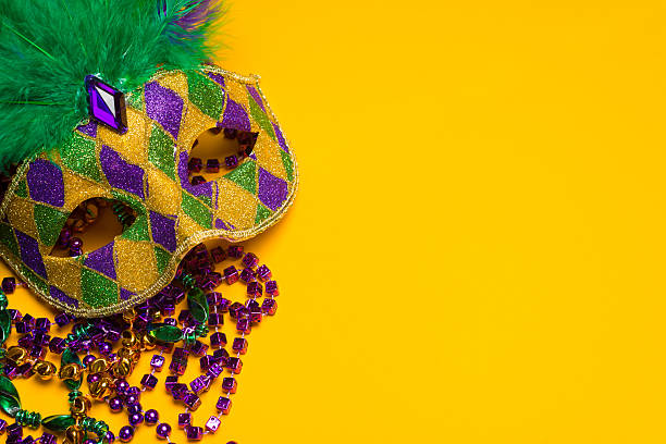 colorful mardi gras or venetian mask on a yellow - carnival stock photos and pictures