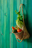 Various colorful contrasting market fresh assorted vegetables in a natural cotton reusable shopping bag hanging from a hook on a vibrant turquoise colored wooden paneled wall background, concept abstract image regarding sustainable lifestyle, reusing materials, organic, environmental awareness, environmental protection, going green, etc.
