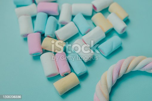 Colorful marshmallow on blue background. Many candies on the table. Twisted marshmallow with candies around.