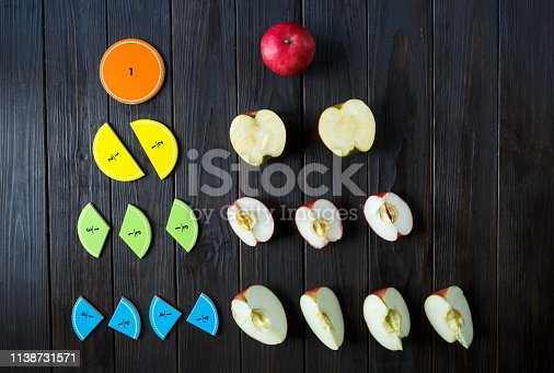 Colorful math fractions and apples as a sample on brown wooden background or table. Interesting math for kids. Education, back to school concept. Geometry and mathematics materials. Fun lessons