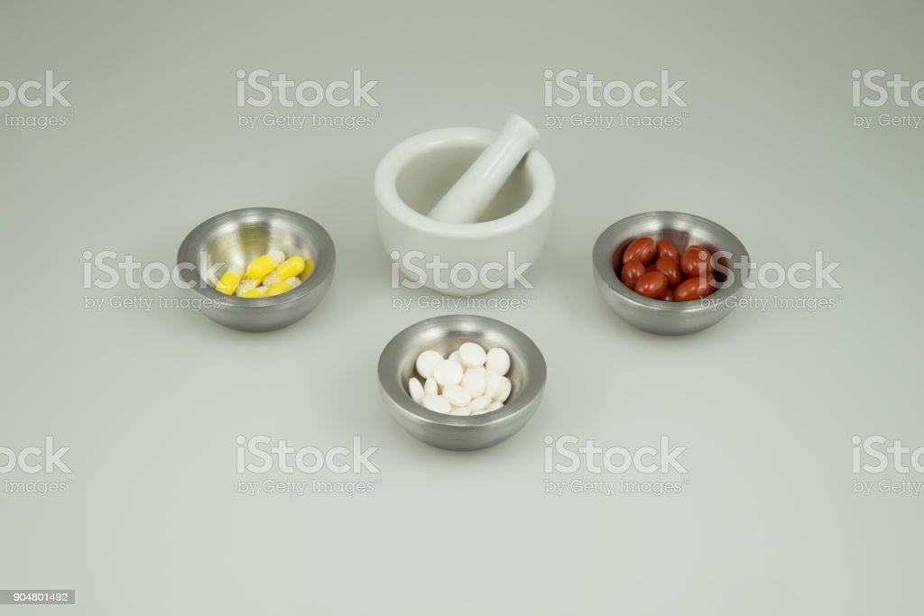 Bunte Medikamente auf einem hellen Hintergrund mit einem Mörser und Stößel – Foto