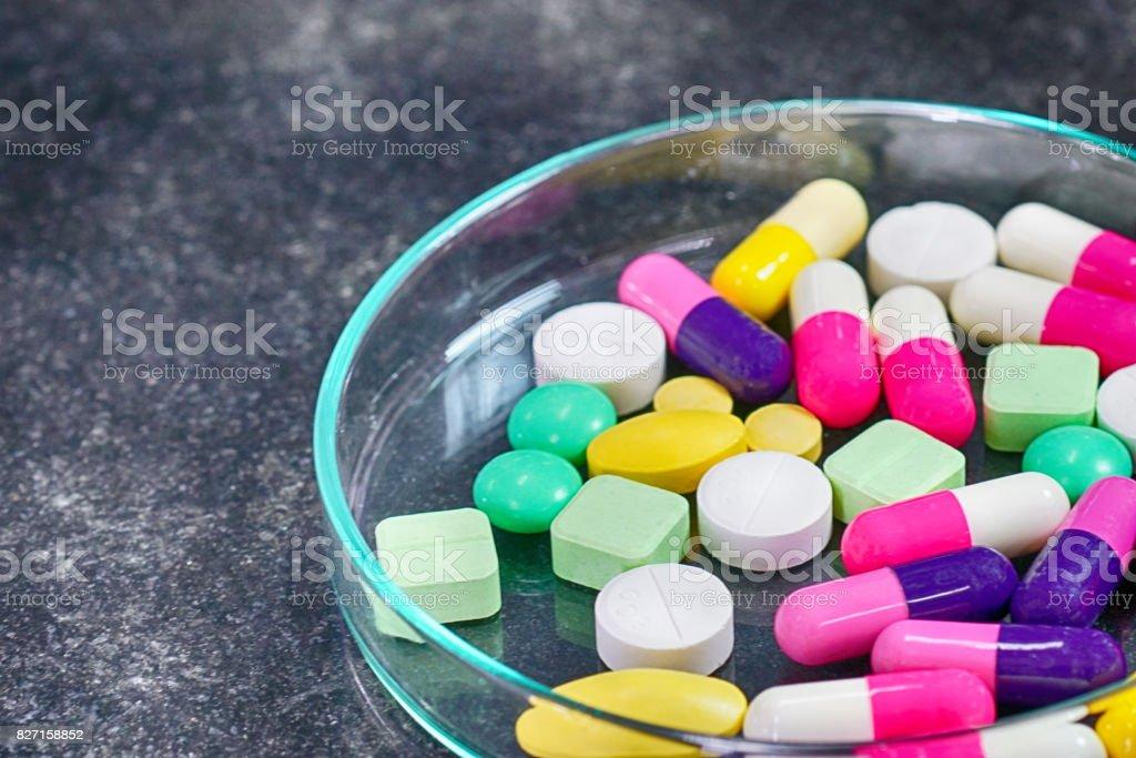 Colorful medicine pills in petri dish on table stock photo