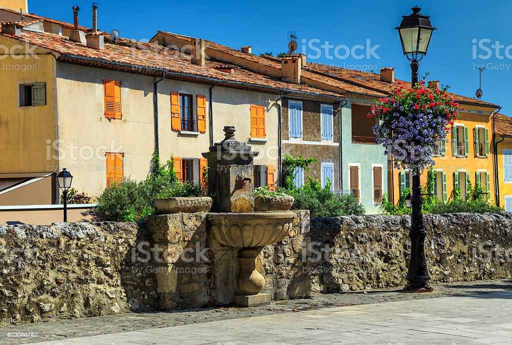 Colorful medieval facades with water fountain in Moustiers-Sainte-Marie stock photo