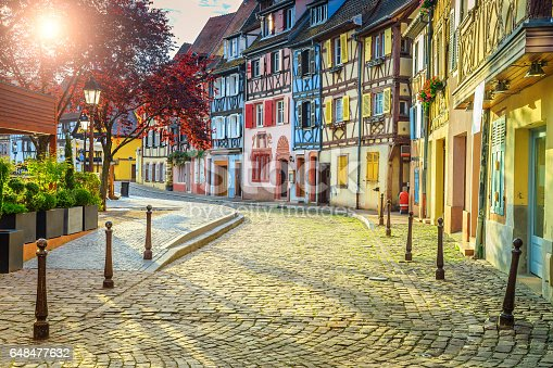 istock Colorful medieval half-timbered facades with paved road in Colmar 648477632