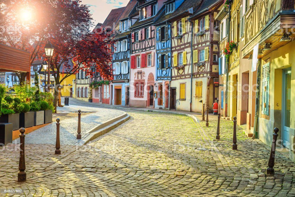 Colorful medieval half-timbered facades with paved road in Colmar stock photo