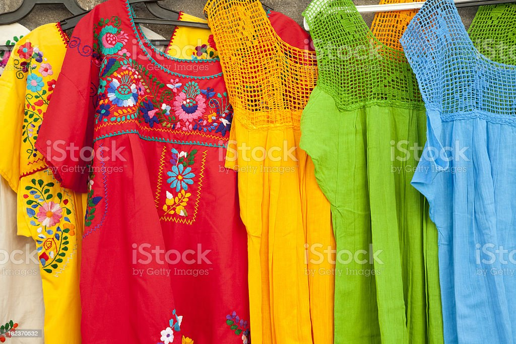 Colorful Mexican Dresses Hanging In Outdoor Market stock photo