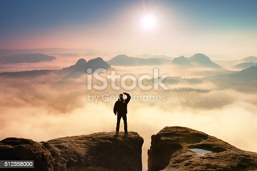 Colorful misty morning in rocks. Tourist in dark cloths on rock empire shadowing eyes  with hand in the air.