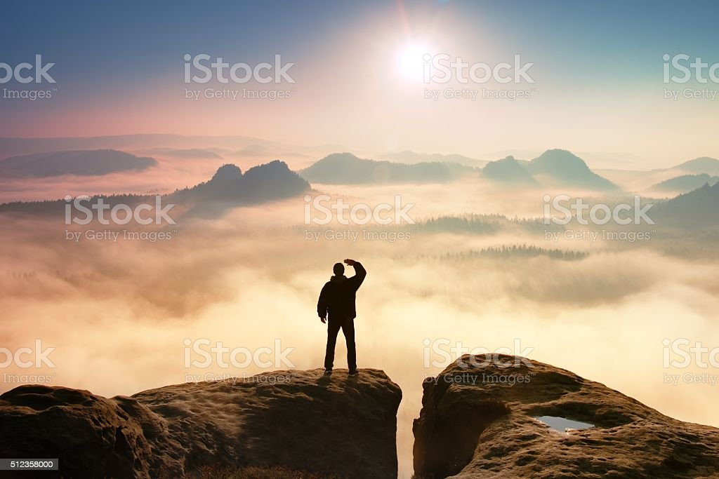 Colorful misty morning. Tourist in dark cloths in rocks stock photo