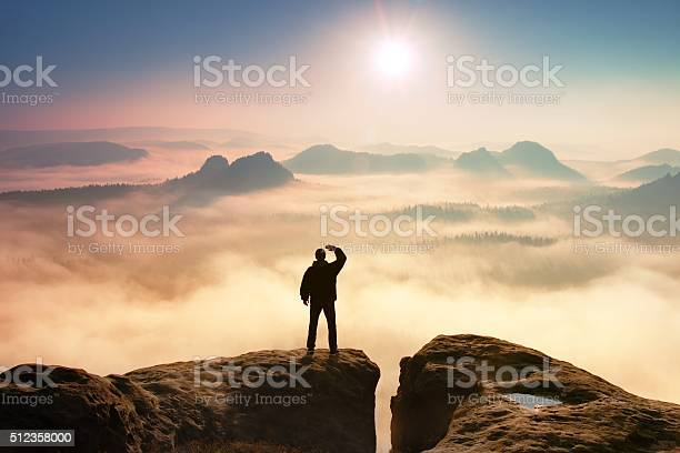 Photo of Colorful misty morning. Tourist in dark cloths in rocks