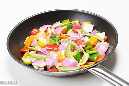 Colorful and fresh vegetables in a non-stick frying pan on a white background (red, green and orange bell peppers, onions, green beans and celery). More vegetables...