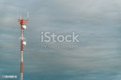istock Colorful mobile phone network telecommunication towers against blue sky background. Concept of telecom, telco, connectivity, and technology 1136498916