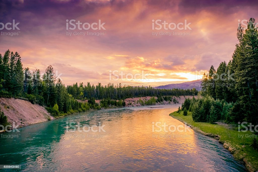 Colorful Montana Sunset in Glacier National Park Over River Scene stock photo