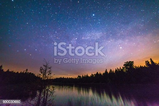 istock Colorful moonrise over a still river at night with milky way, stars and night sky 930030650