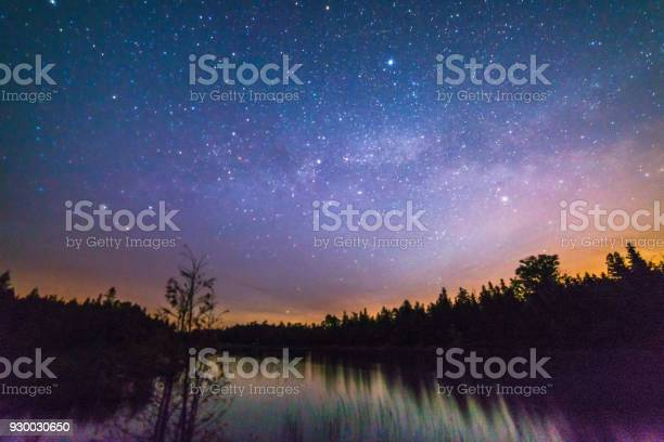 Photo of Colorful moonrise over a still river at night with milky way, stars and night sky
