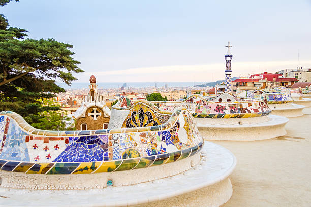 Colorful mosaic benches at the Gaudi-designed Park Guell View of colorful ceramic mosaic bench of park Guell, designed by Antonio Gaudi, in Barcelona, Spain barcelona spain stock pictures, royalty-free photos & images