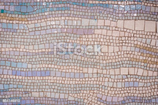 Old distressed mosaic wall background with colorful tiles.