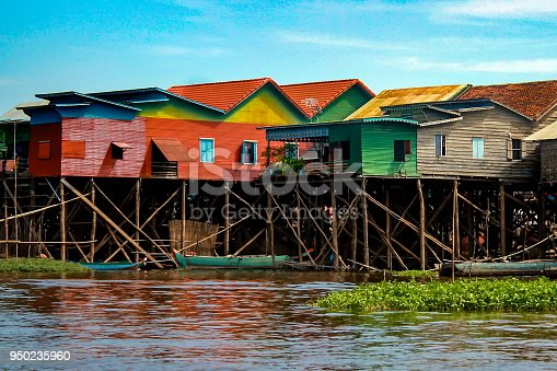 Colorful, multicolored stilt houses line the edge of Lake Tonle Sap in the floating village of Kampong Khleang, near Siem Reap in Cambodia