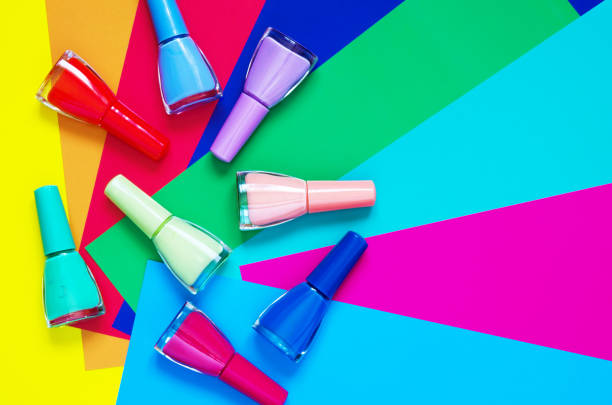 bunte nägel polieren flaschen auf mehrfarbigem papier. das konzept der mode- und schönheitsindustrie. - bild - nägel glitzer stock-fotos und bilder