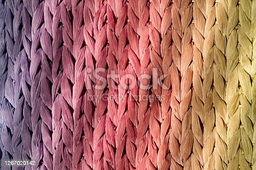 Colorful natural braid illuminated by the sun's rays. A natural material for braiding decorative items. Front view of a hand-woven basket.