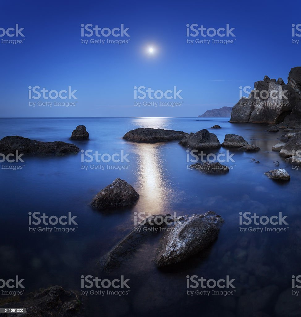 Colorful night landscape with full moon, lunar path and rocks stock photo