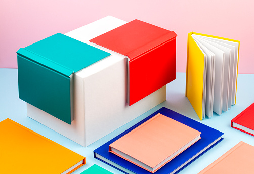 Colorful notebooks over the pastel background. Modern abstract working space, studies, office desk concept