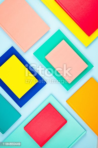 istock Colorful notebooks over the blue pastel background. Modern abstract working space 1184850449