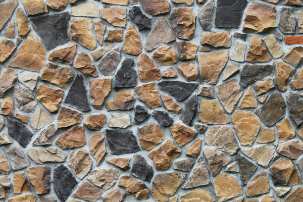colorful odd shaped tan black natural stone block wall with shadows detailed contour shades suitable for website background marketing backgrounds backdrops architecture architectural layout design stock photo
