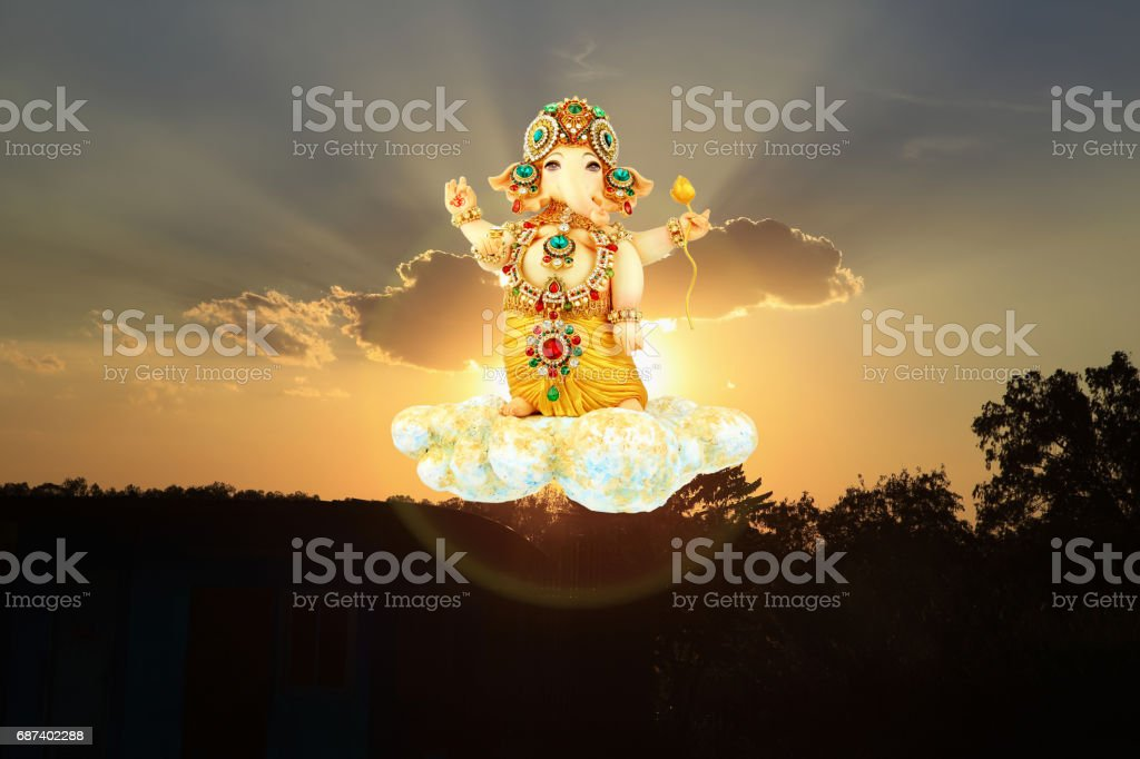 Colorful of Lord Ganesh on cloud stone with sunset and cloud background, warm tone and dark tone. stock photo