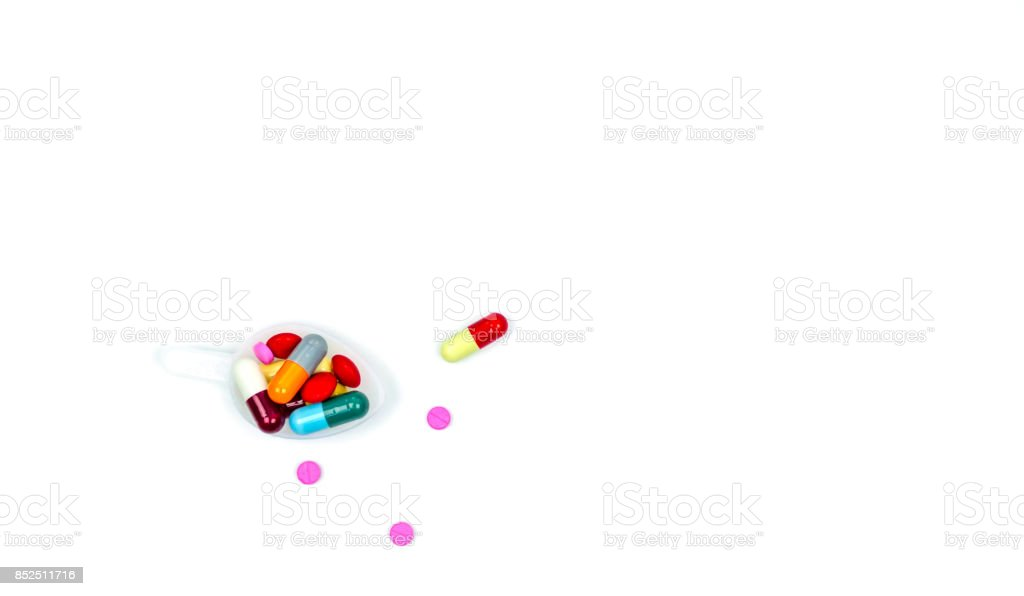 Colorful of tablets and capsules pills in plastic teaspoon and some of them spread on white background with copy space, just add your own text. stock photo